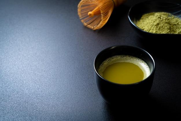 Taza de té verde matcha caliente con polvo de té verde y batidor