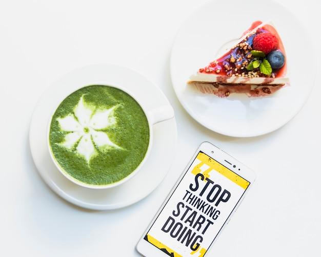 Taza de té verde matcha caliente; tarta de queso y teléfono celular con mensaje en pantalla sobre fondo blanco