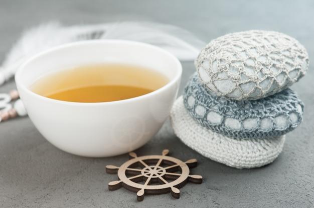 Taza de té verde y piedras de ganchillo