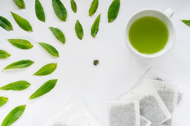 Taza de té verde sobre fondo blanco.