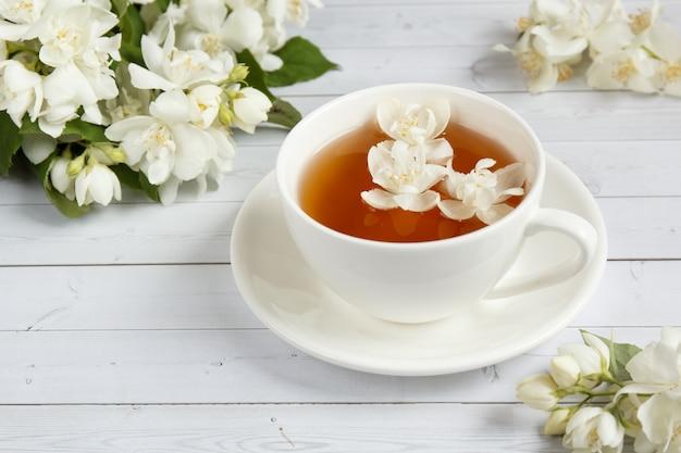 La taza de té, vertiendo la miel de una cuchara en un tarro, flores del jazmín en un fondo de madera ligero.