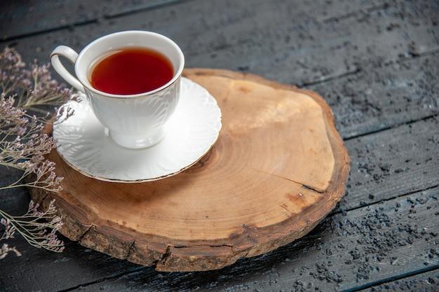 Taza de té vista frontal sobre fondo oscuro