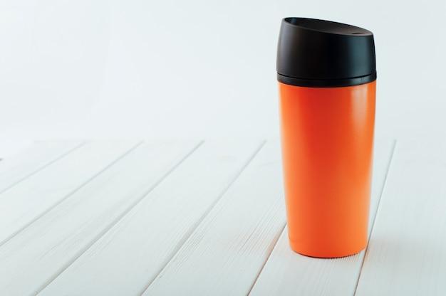 Taza termo naranja sobre mesa de madera blanca.