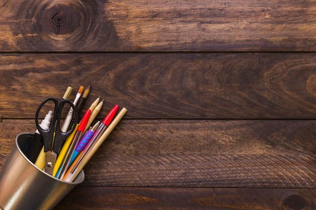 Taza con tijeras y suministros de escritura