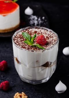 Taza de tiramisú con cacao en polvo y frambuesa con menta.