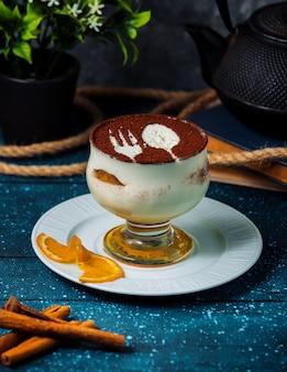 Taza de tiramisú con cacao en polvo y palitos de canela
