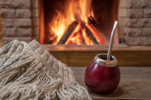 Taza tradicional para beber mate y bufanda de lana, cerca de una acogedora chimenea, en casa de campo ,.