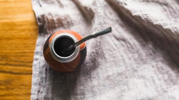 Taza tradicional de yerba mate de pie sobre drapeado