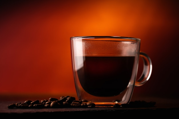 Taza transparente con café negro (americano) con frijoles arábica en una pared roja. macro. de cerca. estilo rústico