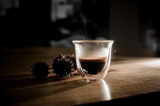 Taza transparente llena de café caliente y aromático.
