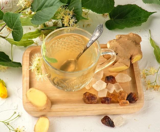 Taza transparente con té de jengibre y tilo en tablero de madera blanco