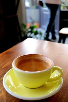 Taza vacía de beber café terminado en la mesa de madera con alguien borroso saliendo de la habitación