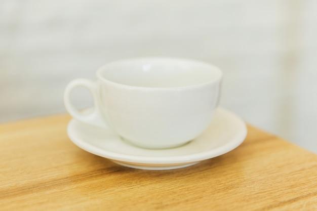 Taza vacía blanca en mesa de madera en un restaurante
