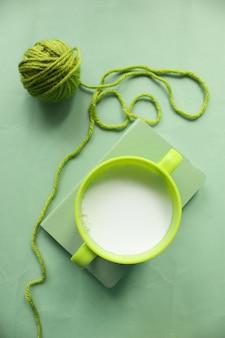 Una taza verde de leche en el libro y una bola de hilo verde en la mesa verde.