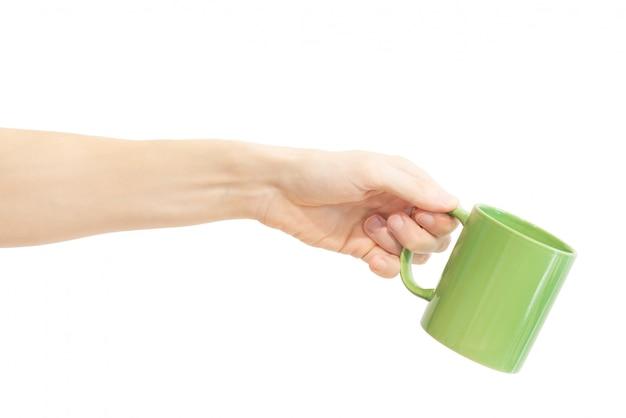 Una taza verde en la mano aislada