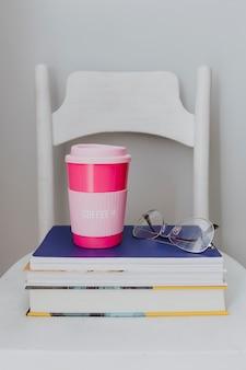 Taza de viaje rosa en una pila de libros de texto