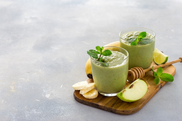 Taza de vidrio con batido de salud verde de manzana, plátano, lima y miel sobre una mesa