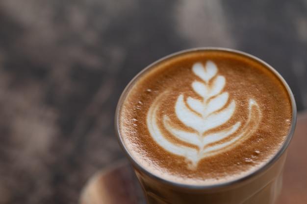 Una taza de vidrio de café latte art en escritorio de madera