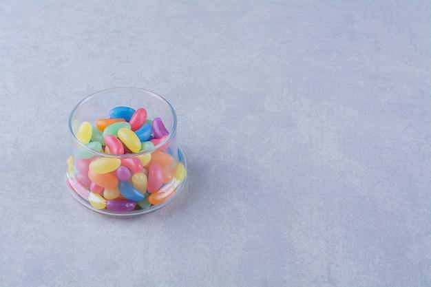 Una taza de vidrio llena de caramelos de frijoles coloridos sobre fondo gris.foto de alta calidad