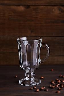 Taza de vidrio vacía para té y café en una mesa de madera.