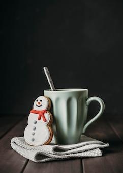 Taza de vista frontal con galleta de muñeco de nieve