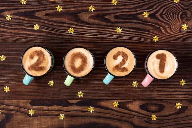 Tazas de año nuevo de café con leche o capuchino con dígitos en la mesa de madera