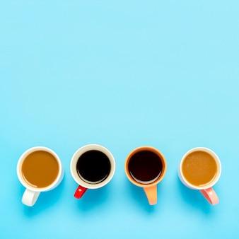 Tazas con bebidas calientes, café, capuchino, café con leche sobre una superficie azul. concepto de cafetería, reunión de amigos, desayuno con amigos, equipo amable. cuadrado. vista plana, vista superior