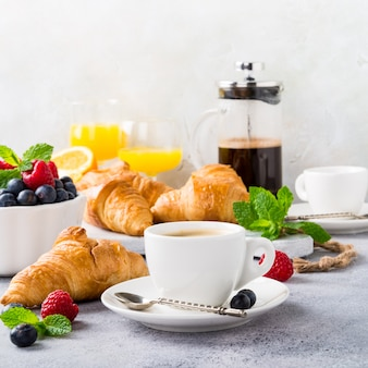 Tazas blancas de café y croissants.