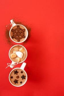Tazas blancas con chocolate caliente y malvaviscos, y decoración de cacao en polvo con forma de copo de nieve y estrellas