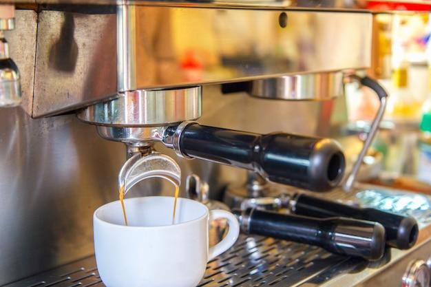Tazas blancas de pie sobre la rejilla de la máquina de café y el café vertiéndose en ellas.