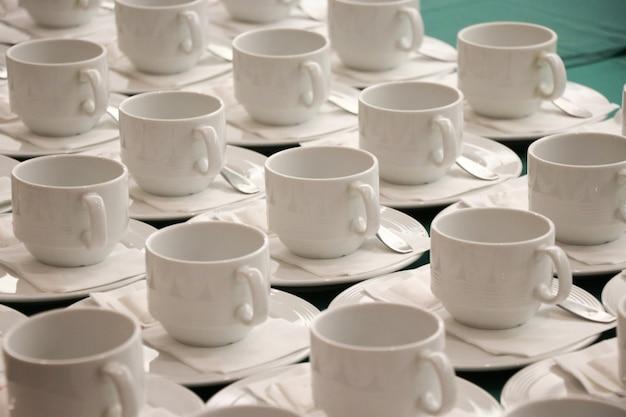 Las tazas blancas vacías con cucharas para café o té caliente colocan a los invitados sobre la mesa