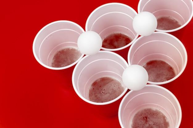 Tazas y bolas de plástico sobre fondo rojo. juego de cerveza pong