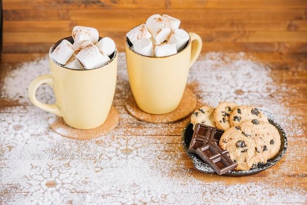Tazas de cacao con dulces en mesa