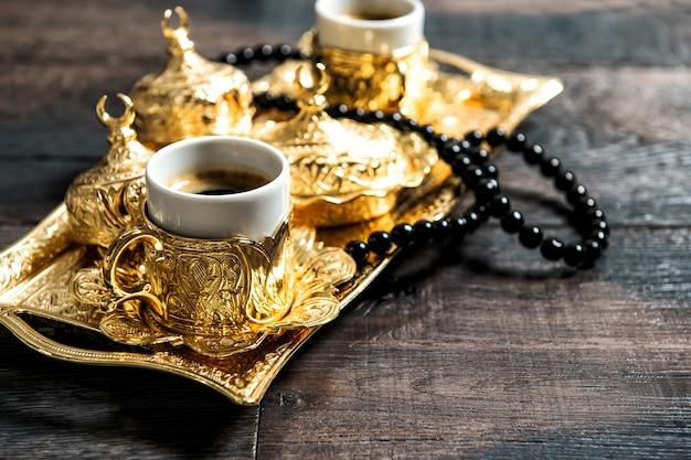 Tazas de café, adornos dorados y rosario sobre fondo de madera oscura.