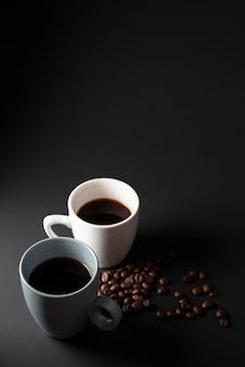Tazas de café de alto ángulo con granos tostados