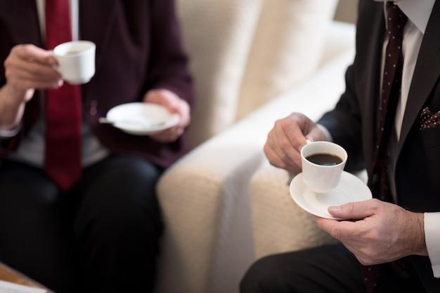 Tazas de café. bonitas tazas de café blancas brillantes en manos de dos personas en la oficina
