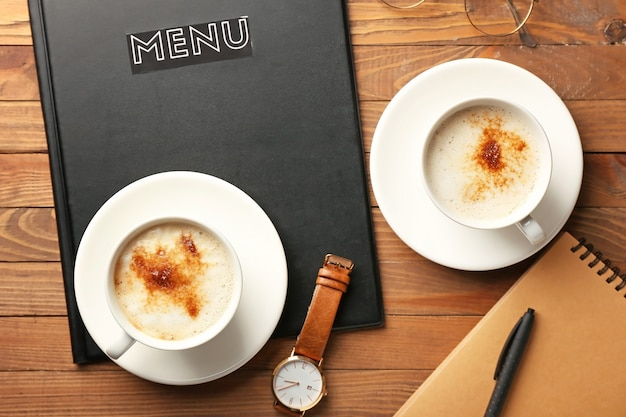 Tazas de café caliente y reloj de pulsera en la mesa de madera en el café