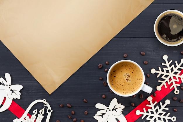 Tazas de café caliente sobre superficie de madera negra en navidad
