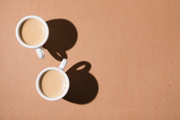 Tazas con café caliente y sombras
