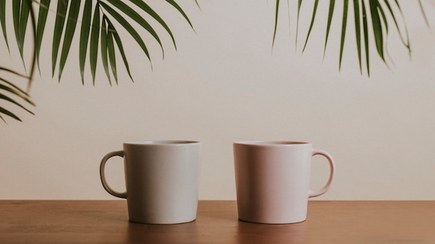 Tazas de café de cerámica de color tono tierra sobre mesa de madera