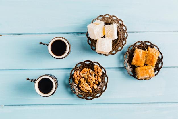 Tazas de café cerca de platillos con dulces postres turcos