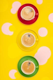 Tazas de café y círculos de papel de colores sobre tabla amarilla