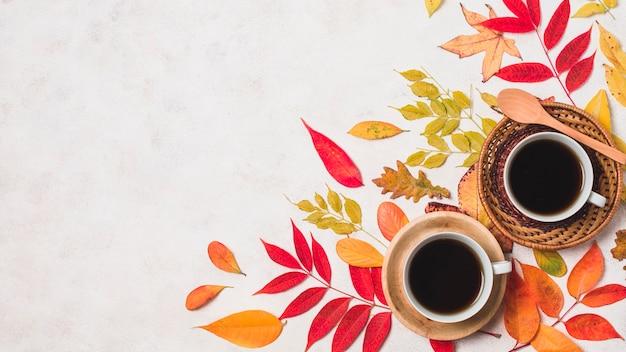 Tazas de café y coloridas hojas de otoño copian espacio