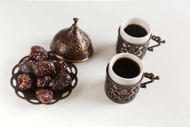 Tazas de café con dátiles en platillo