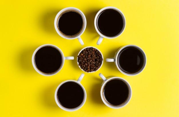 Tazas de café expreso con granos de café sobre fondo amarillo