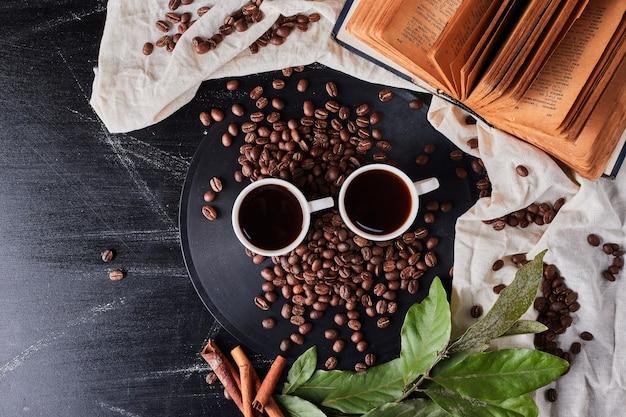 Tazas de café con frijoles alrededor.