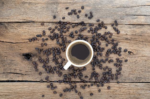 Tazas de café y granos de café en el escritorio, vista superior