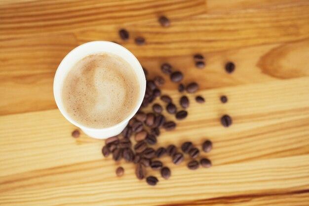 Tazas de café y granos de café en la mesa de madera