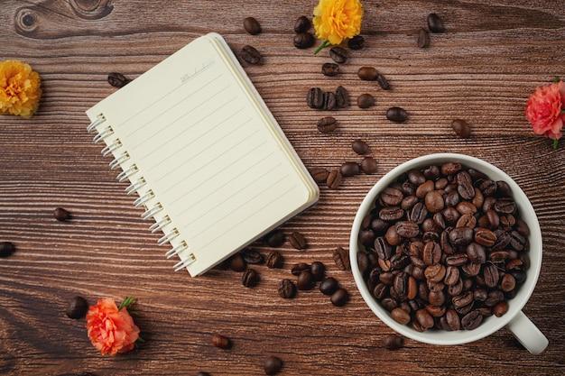 Tazas de café y granos de café sobre la mesa, día internacional del concepto de café