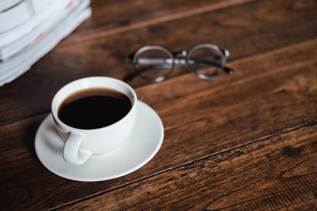 Tazas de café y libros colocados en viejas mesas de madera